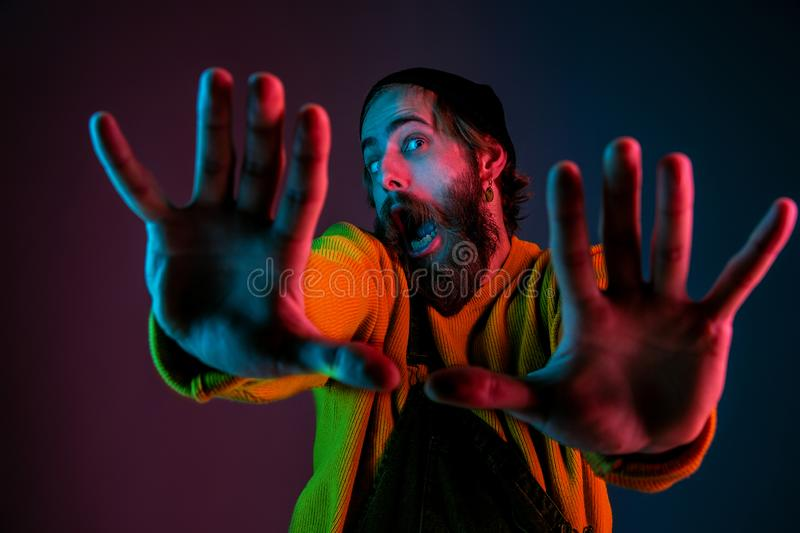 Caucasian man`s portrait isolated on gradient studio background in neon light royalty free stock photography