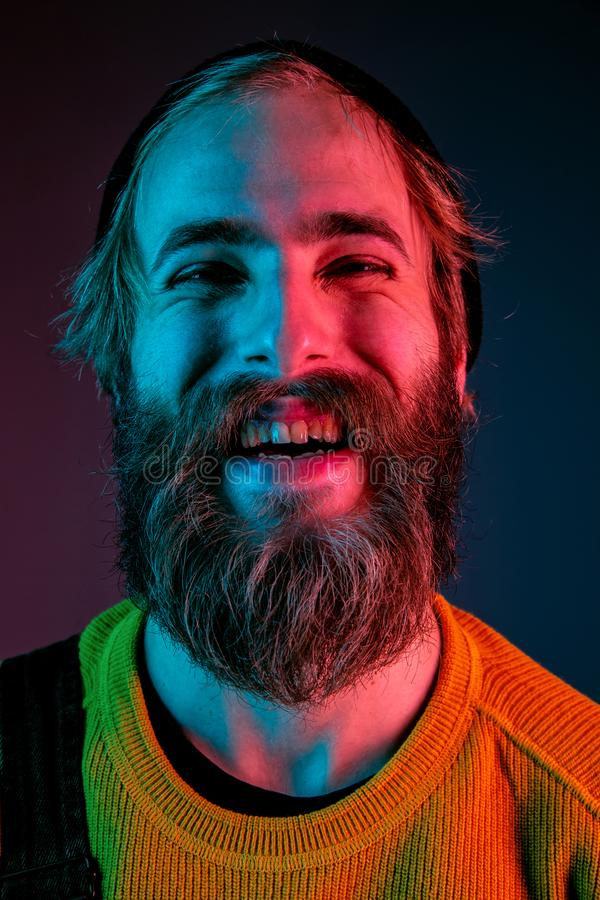 Caucasian man`s portrait isolated on gradient studio background in neon light royalty free stock image
