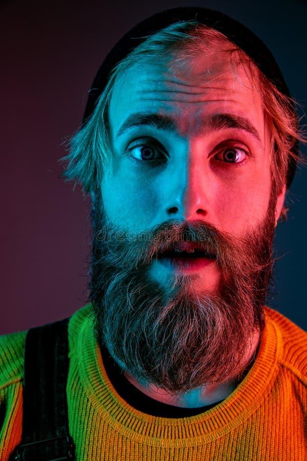 Caucasian man`s portrait isolated on gradient studio background in neon light stock photo