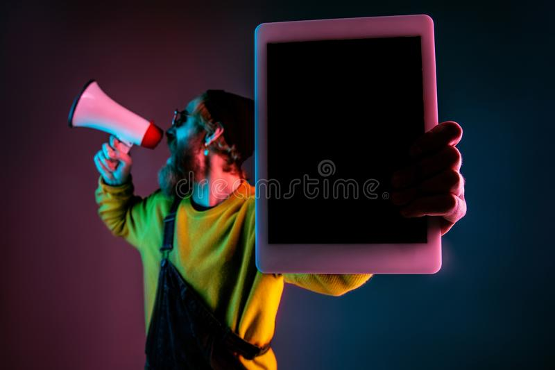 Caucasian man`s portrait isolated on gradient studio background in neon light royalty free stock images