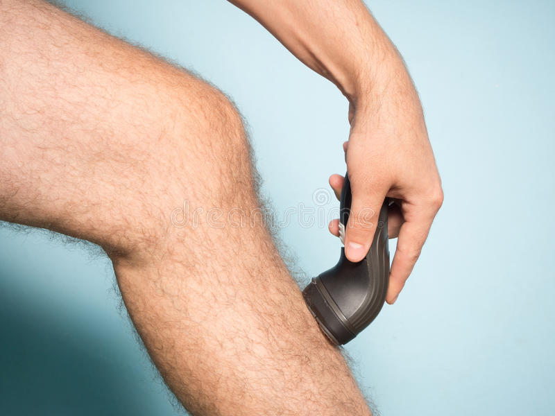 Caucasian man shaving hair from legs royalty free stock image