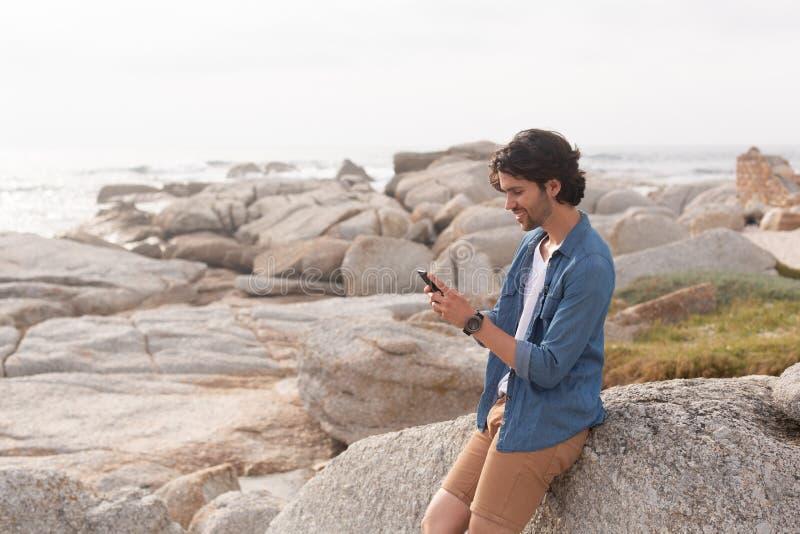 Caucasian man som använder mobiltelefonen på stranden, medan luta på vagga arkivbilder