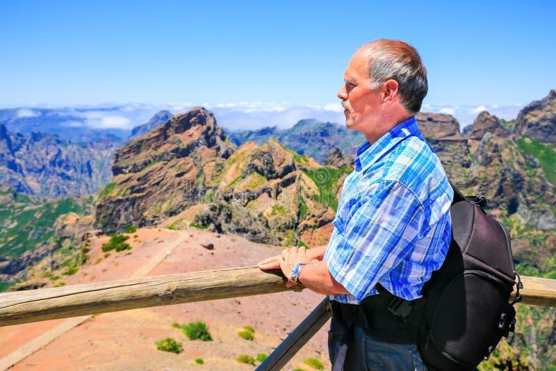 Caucasian man som beskådar steniga berg i landskap royaltyfri bild