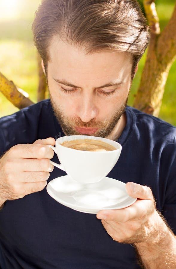 Caucasian man som dricker kaffe i trädgården arkivfoto