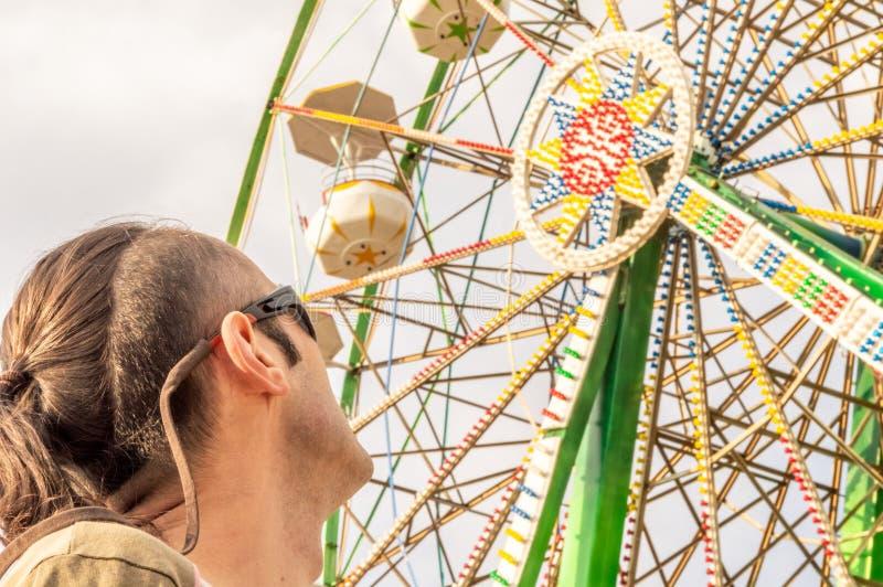 Caucasian man som håller ögonen på ferrishjulet royaltyfri fotografi
