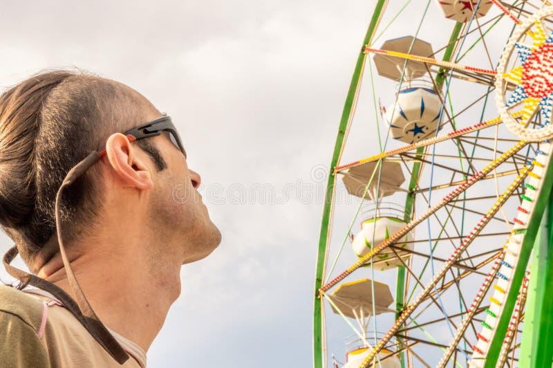 Caucasian man som håller ögonen på ferrishjulet royaltyfria bilder