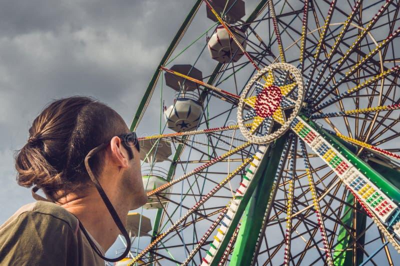 Caucasian man som håller ögonen på ferrishjulet arkivfoto
