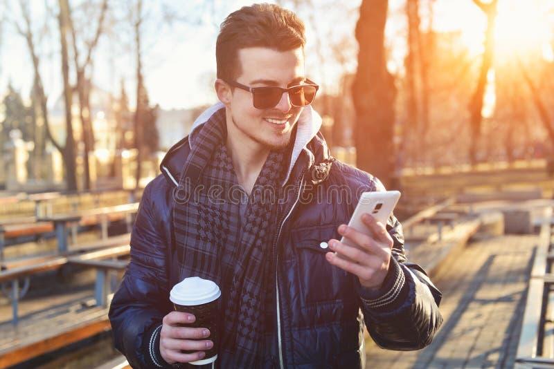 Caucasian man som ser mobiltelefonen på gatan royaltyfri foto