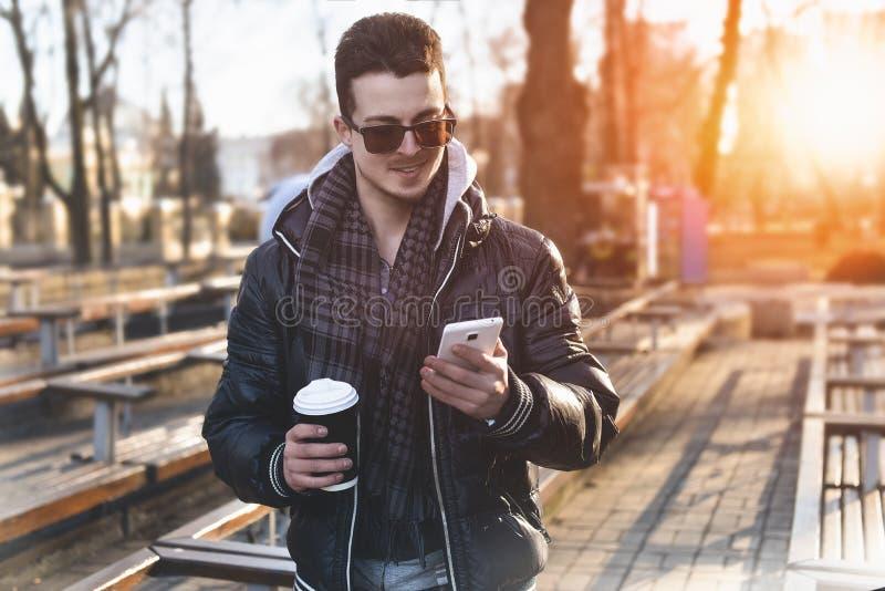 Caucasian man som ser mobiltelefonen på gatan royaltyfria foton