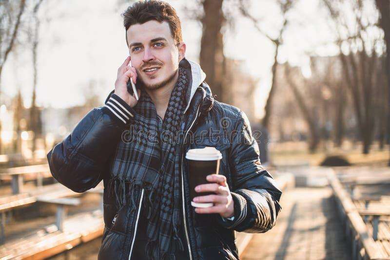 Caucasian man som ser mobiltelefonen på gatan arkivfoto