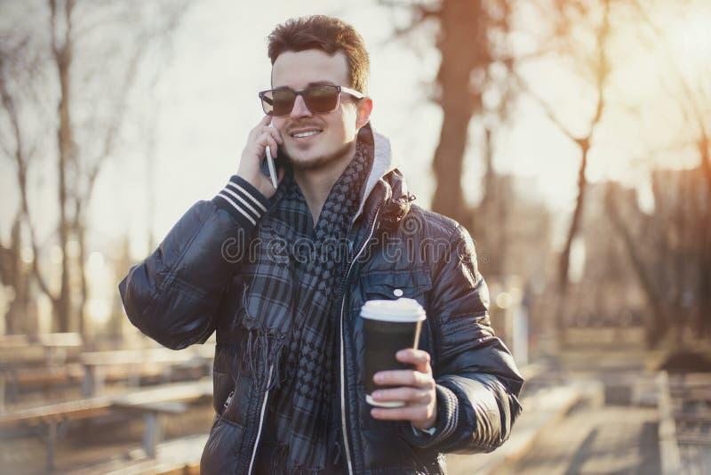 Caucasian man som ser mobiltelefonen på gatan arkivbilder