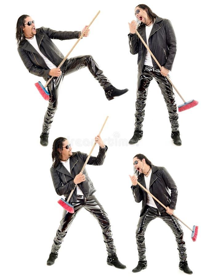 Caucasian man som spelar kvasten som gitarren mot arkivfoton