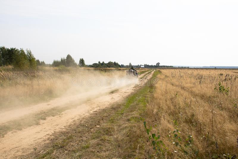 Man riding an ATV quad bike over rough terrain with meadows of dry autumn grass. Caucasian man in sport protective costume riding an ATV quad bike over rough royalty free stock photo