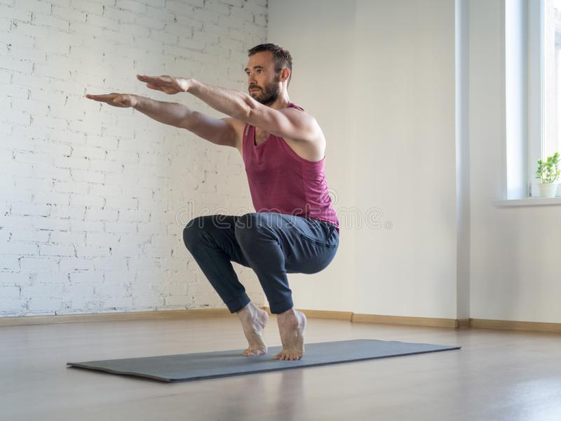 Caucasian man stands on tiptoe and practice yoga in fitness studio, loft style, selective focus. Chair pose. Pilates, workout, smart body, exercise therapy stock photo