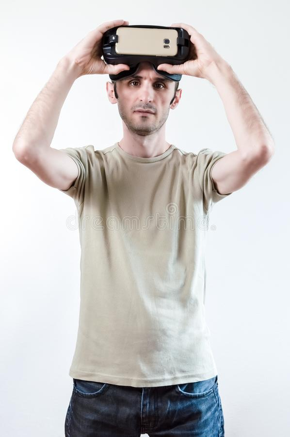 Portrait of a handsome brunet man with virtual reality goggles on head on white background stock photo