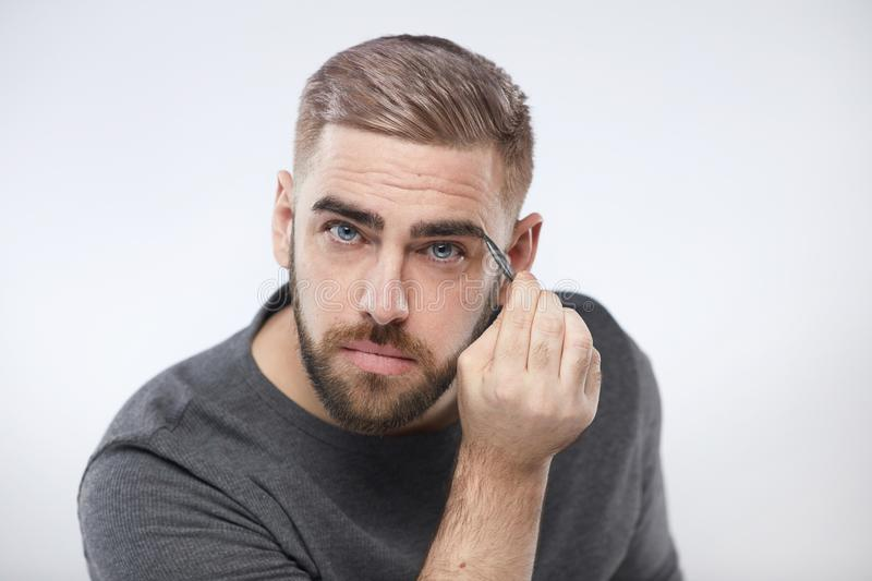 Caucasian Man Tweezing Eyebrows stock photo