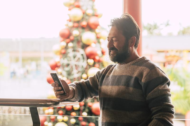 Caucasian man using mobile phone in winter christmas period with tree in background at commercial mall center for shopping and buy royalty free stock photo