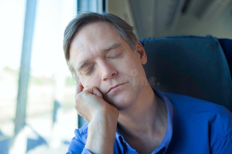 Caucasian man in blue shirt sleeping against train window royalty free stock photo