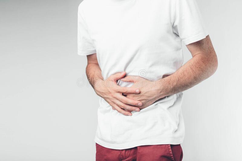Caucasian man in white T-shirt and burgundy pants. Holding his hands on stomach. Cut view. Concept. Belly hurts. Over light background royalty free stock images