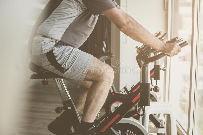 Caucasian man working out on elliptical machine. Close up stock photo