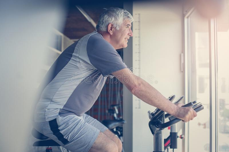 Caucasian man working out on elliptical machine. Routine stock photos