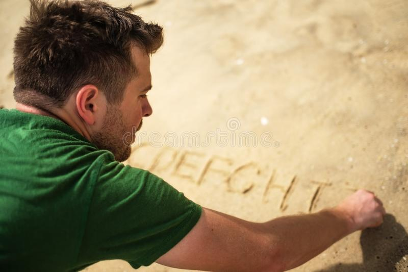 Caucasian man writing on sand alphabet letters. royalty free stock images