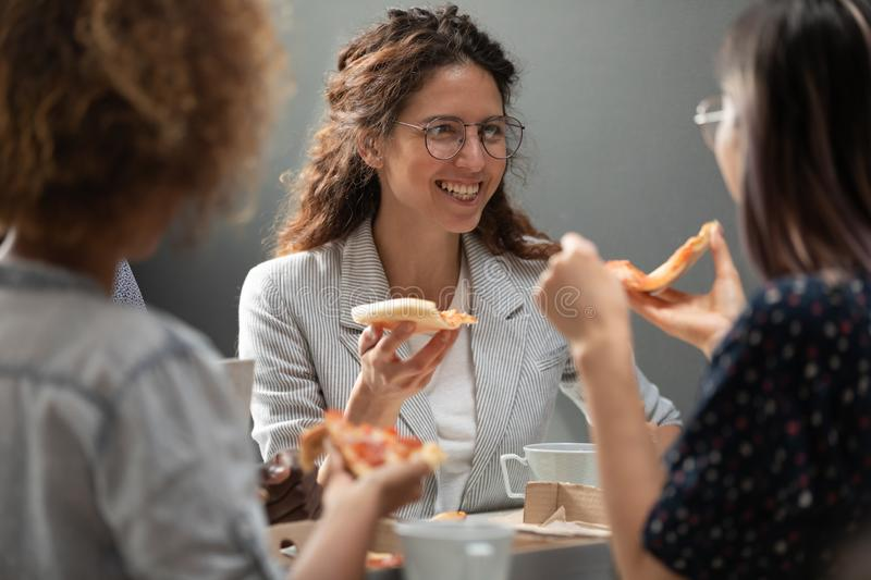Caucasian manager sharing lunch with mixed race teammates. stock photos
