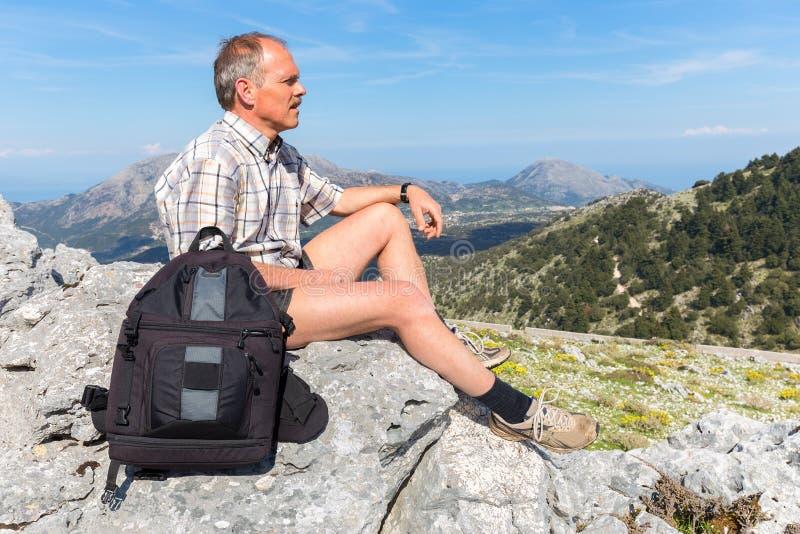 Caucasian mansammanträde med ryggsäcken i grekiska berg royaltyfria bilder