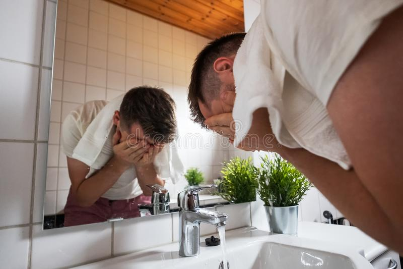 Caucasian mantvagningframsida i en tvättställ i den vita toaletten arkivfoton