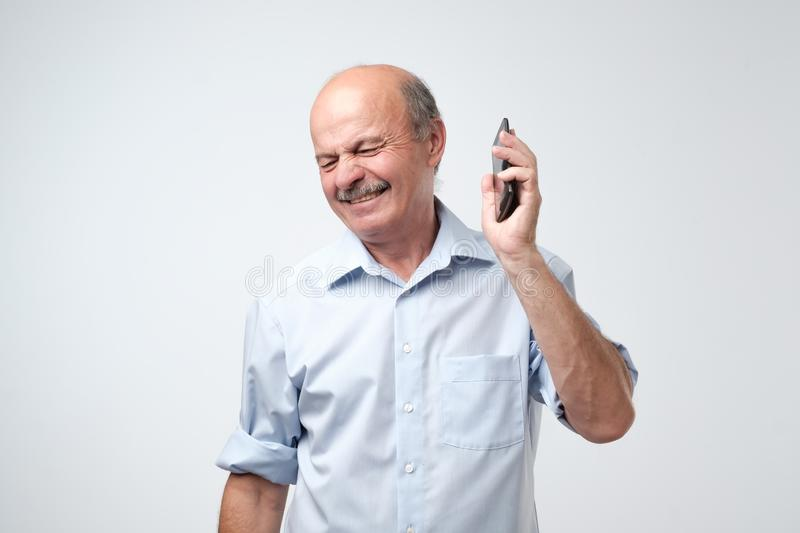 Caucasian mature man is irritated with phone conversation. royalty free stock photo
