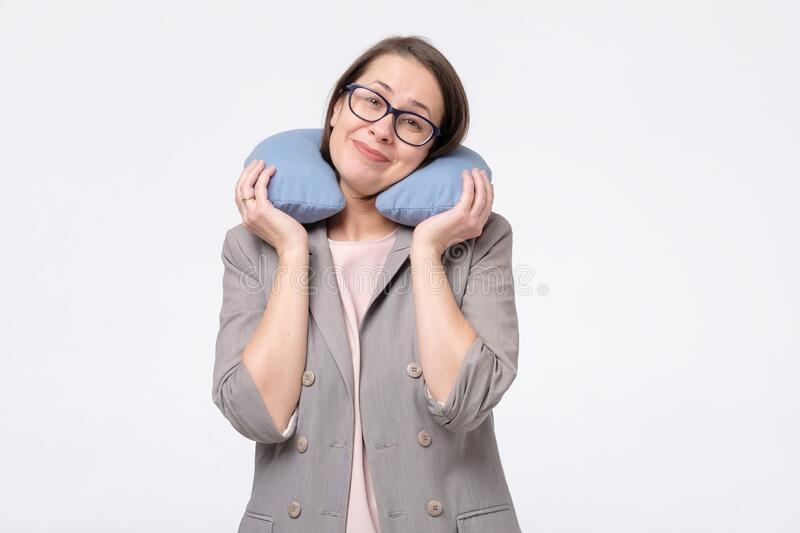 Caucasian mature woman smiling holding travel pillow on neck travelling in comfort. royalty free stock images
