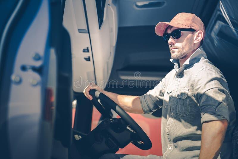 Men Driving Semi Truck. Caucasian Men Driving Semi Truck. Trucker in His 30s Inside Semi Tractor Cabin royalty free stock photo