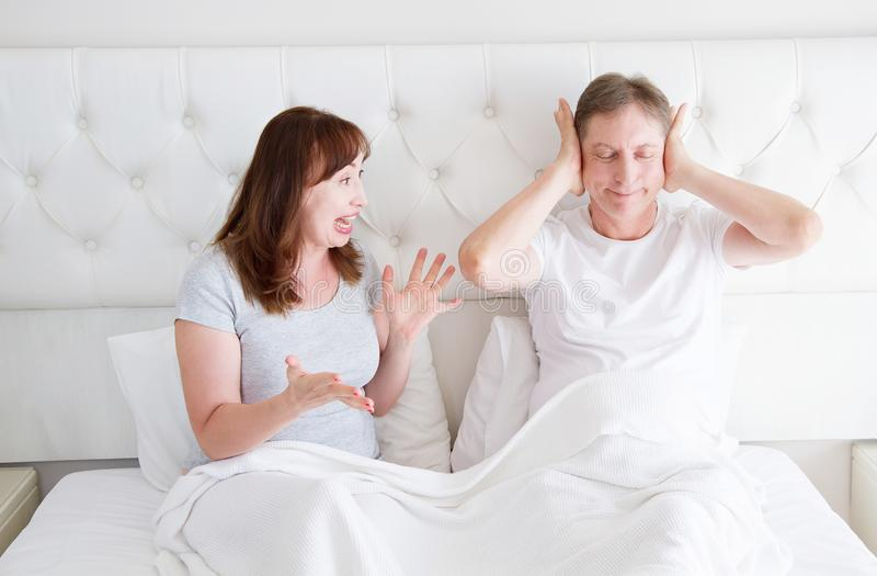Caucasian middle age family couple angry shouting in bed. Conflict relationship concept. Husband cover ears by hands and wife. Trying make a dialogue. Selective stock photos