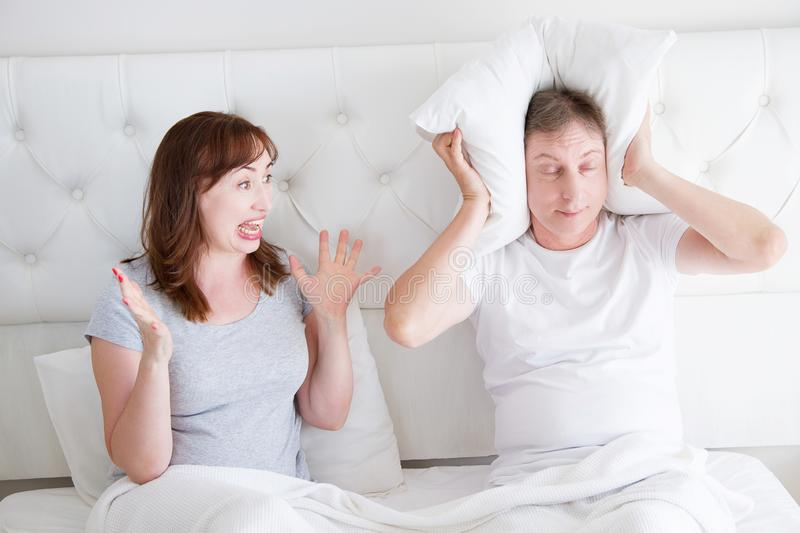Caucasian middle age family couple angry shouting in bed. Conflict relationship concept. Husband cover ears by hands and wife. Trying make a dialogue. Selective stock photo