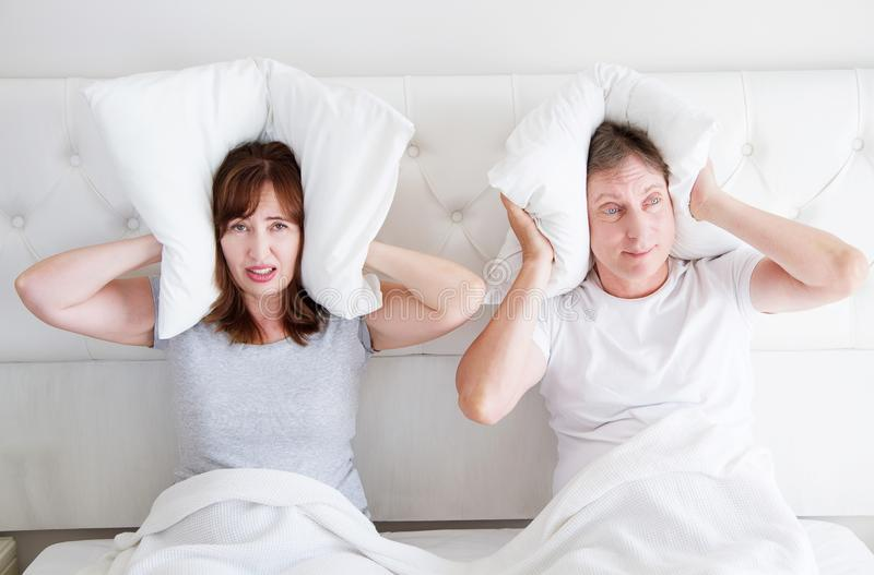 Caucasian middle age family couple angry shouting in bed. Conflict relationship concept. Husband and wife cover ears by pillow. Selective focus stock photo