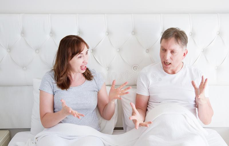 Caucasian middle age family couple angry shouting in bed. Conflict relationship concept. Husband and wife dialogue. royalty free stock photos