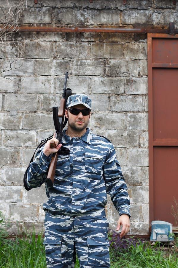 Caucasian military man with black sunglasses in urban warfare ho stock photography
