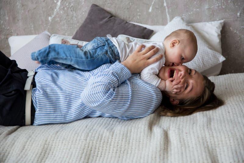 Caucasian moder och dotter som ligger på säng arkivfoto