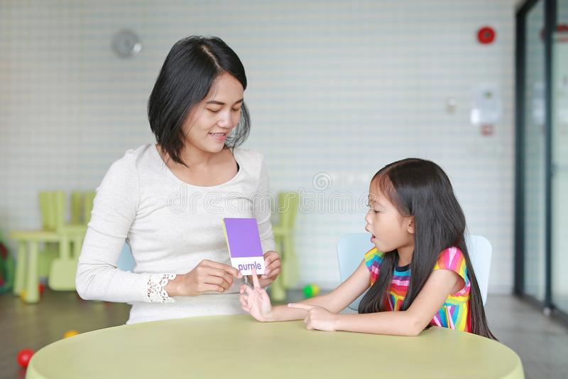 Caucasian mom and daughter playing flash card for Right Brain Development at the playroom. Child learning concept stock photo