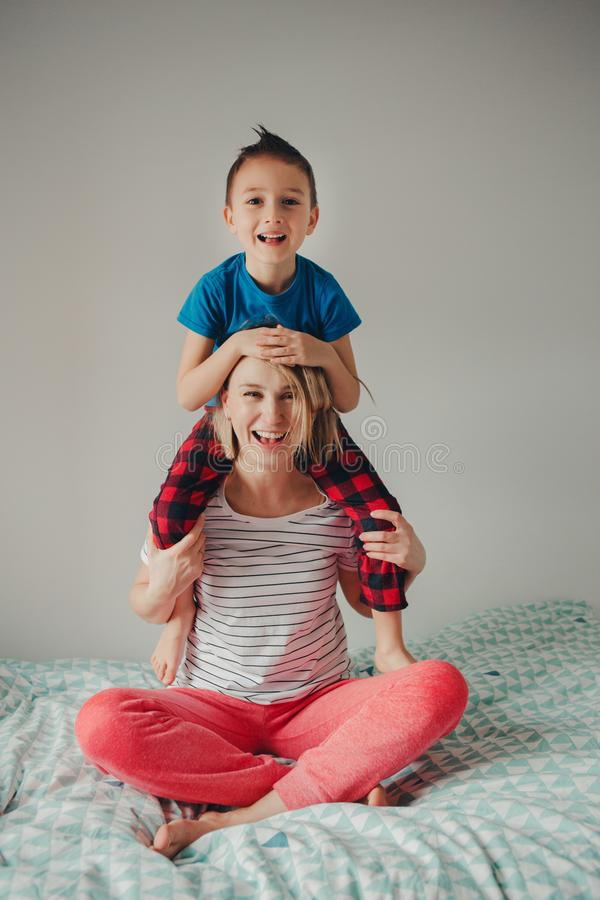 Caucasian mother and boy son playing together in bedroom at home royalty free stock photos