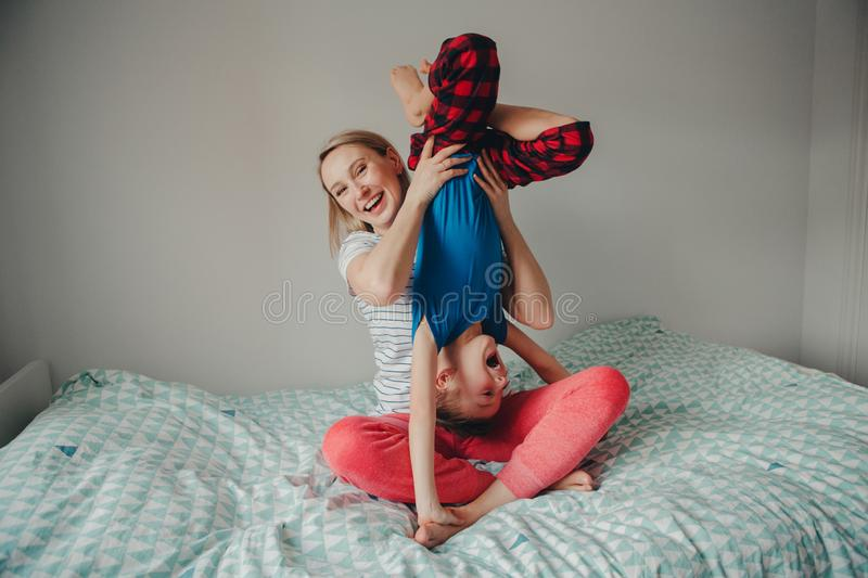 Caucasian mother and boy son playing together in bedroom at home royalty free stock image