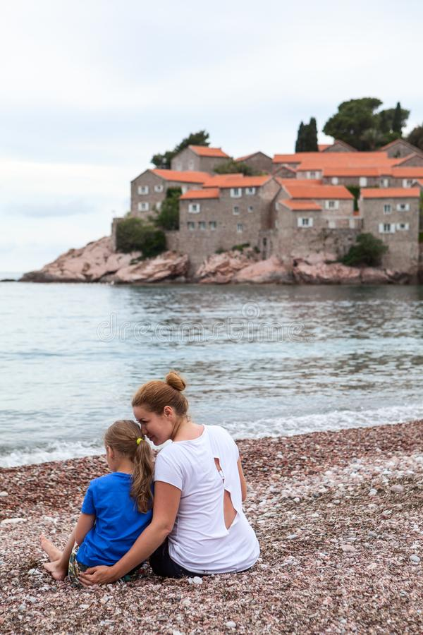 Caucasian mother and daughter sitting together on the luxury beach against Sveti Stefan hotel and resort. Adriatic sea, Montenegro royalty free stock images
