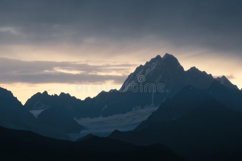 Caucasian mountains silhouettes. At the rising sun. Warm yellow and orange abstract background. Svaneti, Georgia royalty free stock photos