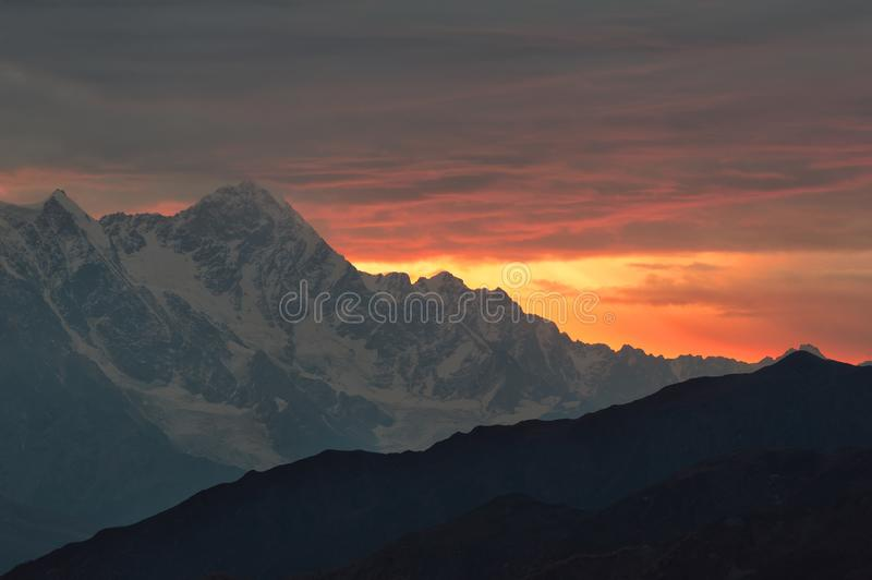 Caucasian mountains silhouettes. Caucasus mountains silhouettes at the rising sun. Warm yellow and orange abstract background. Svaneti, Georgia stock images