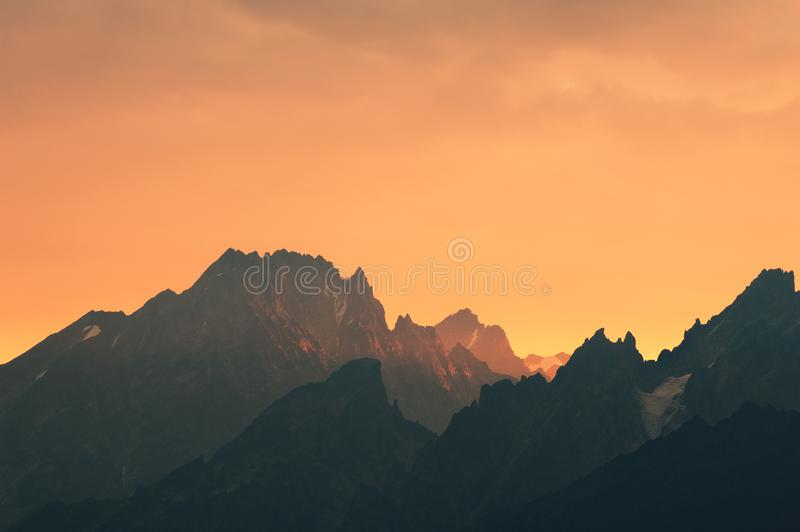 Caucasian mountains silhouettes. Caucasus mountains silhouettes at the rising sun. Warm yellow and orange abstract background. Svaneti, Georgia royalty free stock image