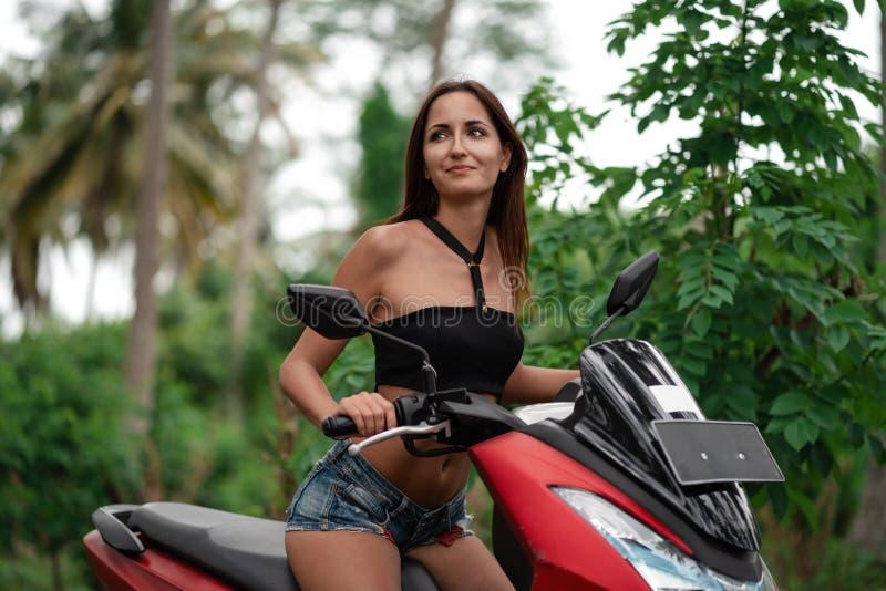 Caucasian nationalitet för brunbränd flicka som kör en röd otorcycle resa på en sparkcykel arkivbild