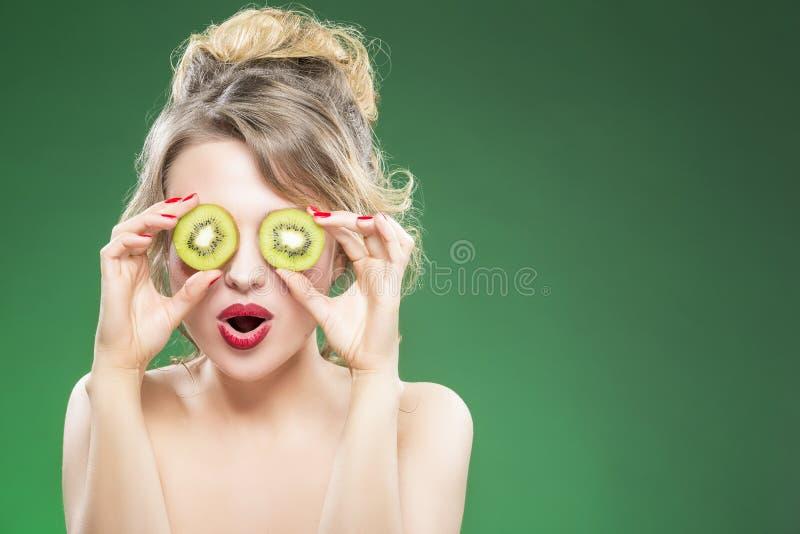 Caucasian Nude Model Making Faces while Posing With Two Kiwi Slices. Kiwi Fruit Series. Smiling Caucasian Nude Model Making Faces while Posing With Two Kiwi royalty free stock photo