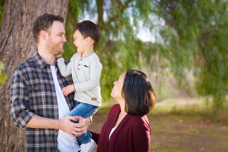 Caucasian och kinesisk familjstående för ungt blandat lopp utomhus royaltyfria foton