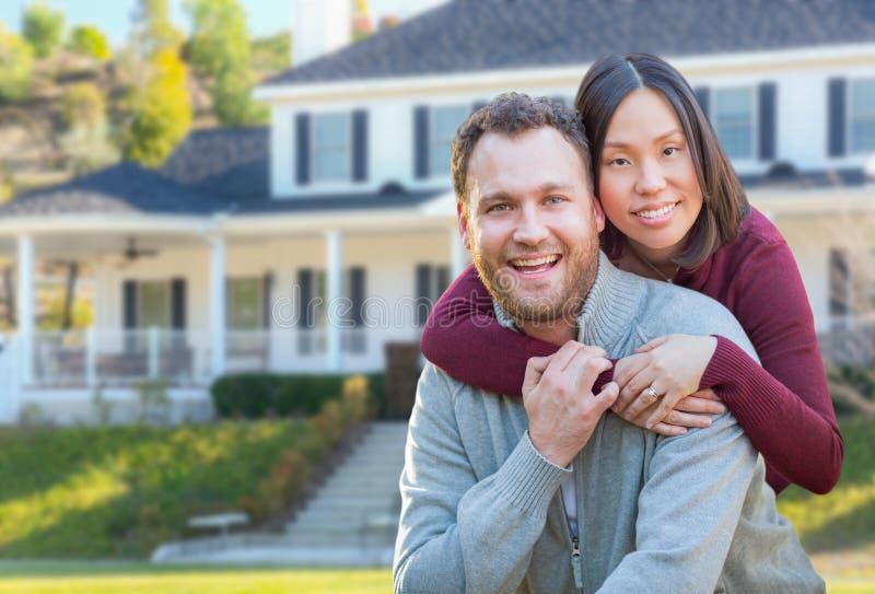 Caucasian och kinesiska par för ungt blandat lopp i Front Yard av ett hus royaltyfri bild