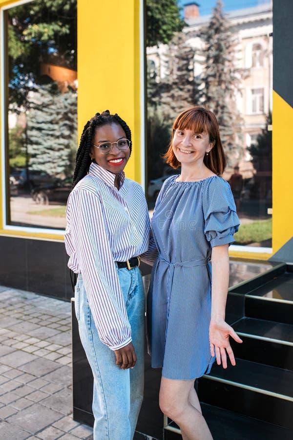Caucasian och muslimska kvinnor, bästa vän som poserar på kameran på gatan arkivbilder